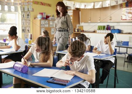 Teacher walking in her busy primary school classroom