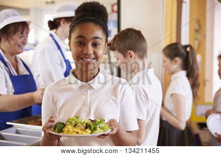 Black schoolgirl holds a plate of food in a school cafeteria