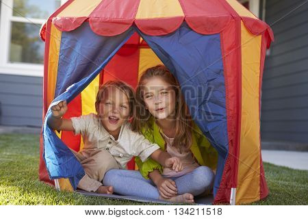 Two Children Playing Inside Tent In Garden Together
