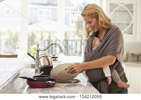 Busy Mother With Baby In Sling Multitasking At Home