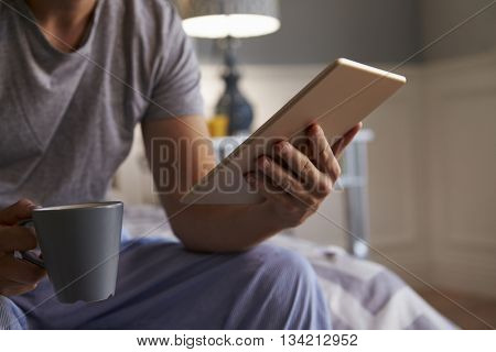 Close Up Of Man In Pajamas Looking At Digital Tablet