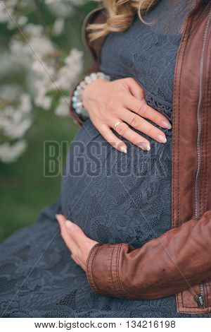 sitting pregnant woman embraces his stomach and hands