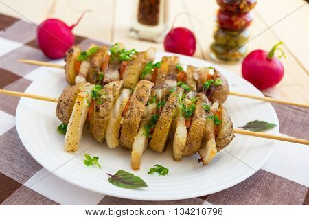 Homemade potatoes baked on a thin stick with bacon and herbs on a white plate on a wooden background.