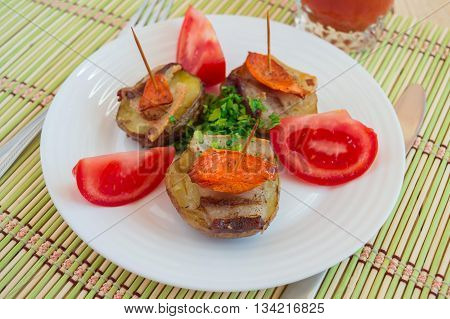 Baked potatoes at home with vegetables and tomato