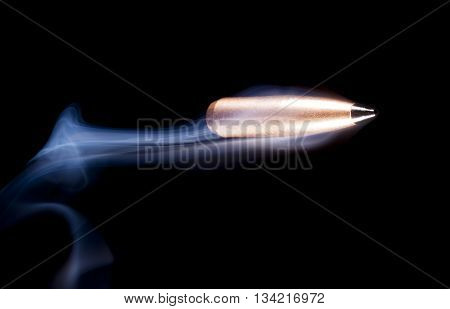Polymer tipped and copper plated bullet with smoke on black