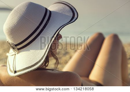Woman wearing bikini and a straw hat lying on the sand on the beach and sunbathing. Summer vacations travel relaxation time. Focus on the hat