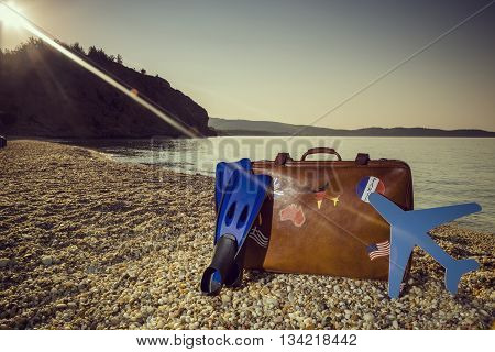 Vintage suitcase with flag stickers fins and a cardboard plane places next to it on the beach with peaceful sea during sunrise on Thassos island in Greece