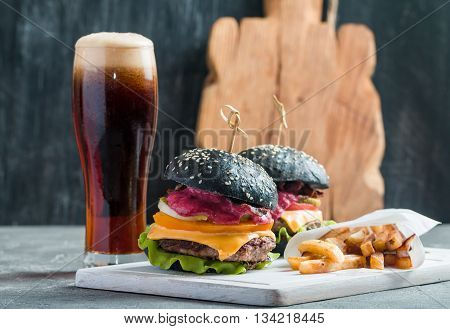 Homemade burger with black bun, beef meat and red berries sauce with glass of dark beer and French fries over dark background.