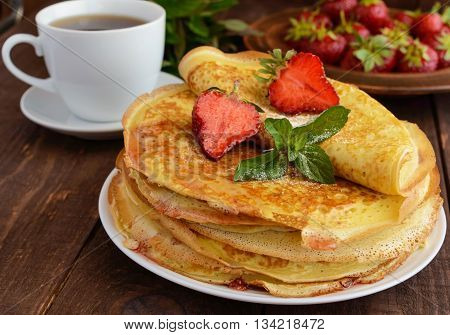 Pile of golden pancakes with strawberries and strawberry jam decorative sprig of mint and cup of tea. Close-up