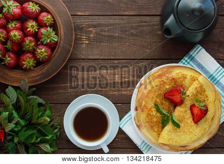 Pile of golden pancakes with strawberries and strawberry jam decorative sprig of mint. The top view