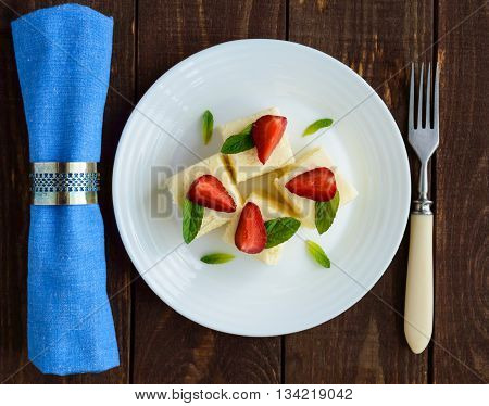 Delicate cottage cheese and creamy souffle in the form of cubes decorating with mint leaves and fresh strawberries on a white plate.
