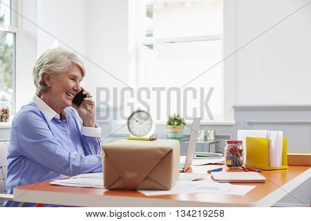 Senior Woman At Home Booking Courier Collection For Package