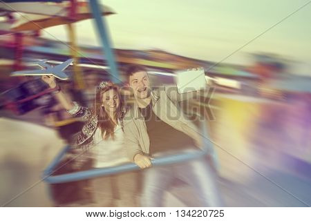 Young couple in love having fun and taking selfie while riding on merry go round in an amusement park