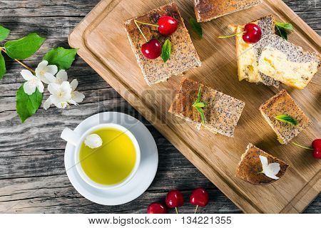homemade cheesecake with poppy seeds on a cutting board on an old wooden table with fresh cherries a cup of jasmine tea and fresh jasmin flowers close-up