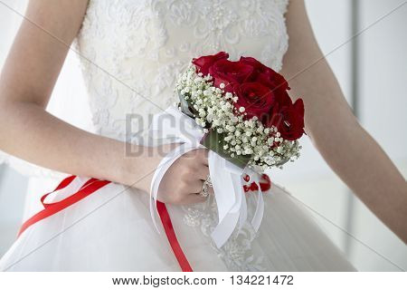 wedding couple hugging, the bride holding a bouquet of flowers in her hand, the groom embracing her. Groom and bride together. Wedding couple.