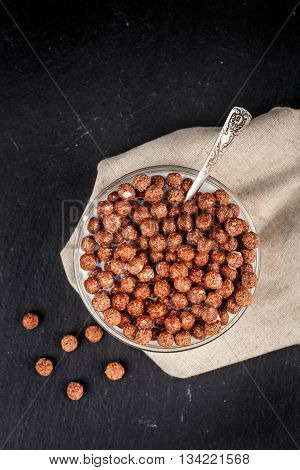 Healthy breakfast. Chocolate cereal balls in bowl with milk on slate background.
