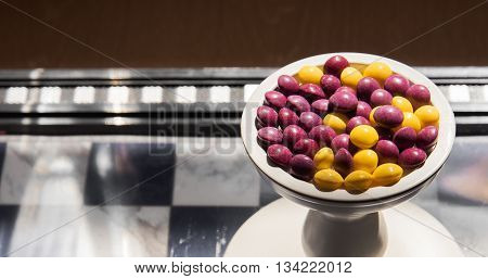 Colorful sweets in a vase on a chess board