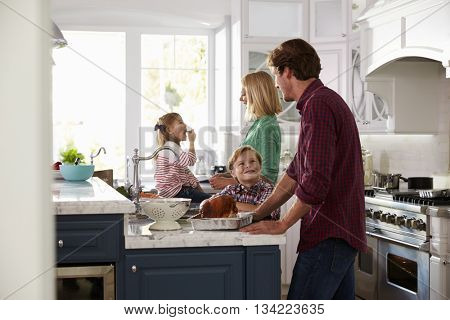 Family Preparing Roast Turkey Meal In Kitchen Together