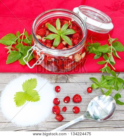 wild strawberries with sugar and preserving jar spoon