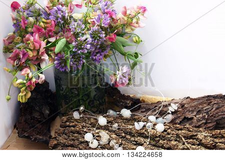 Composition with motley bouquet and white beads