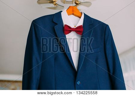 Close-up of excellent expensive blue suit with red bow-tie hanging on luster in the brigtht hotel room interior.