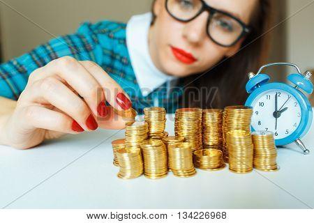 Saving woman stacking gold coins into increasing columns