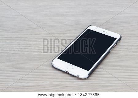 Smart phone with blank screen lying on gray wooden table.