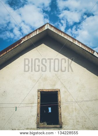 House roof with blue sky and attic opening