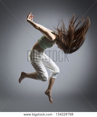 beauty girl jump in dance on grey background