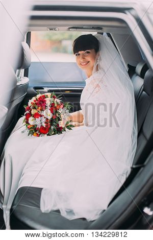 Charming young bride with her bridal bouquet in wedding car limousine.