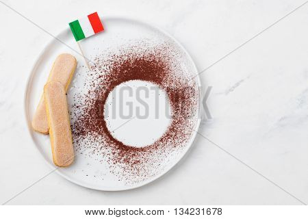 Ingredients for tiramisu dessert with Italian flag on a white plate savoiardi cookies cocoa powder. Copy space. Top view Marble background