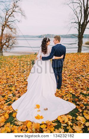 Happy young newlywed bridal couple posing on autumn lakeshore full of orange leaves. Back view