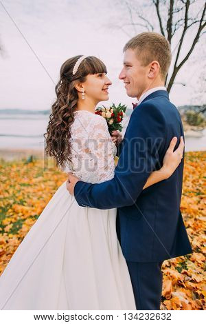 Portrait of happy young newly married couple posing on autumn lakeshore full of orange leaves.
