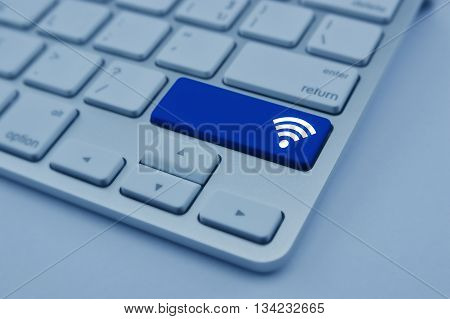 Wi-fi icon on modern computer keyboard button Technology and internet concept blue tone