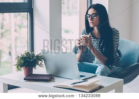 Confident woman at working place. Confident young beautiful woman working on laptop and looking at camera while sitting at her working place