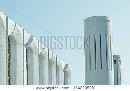 Urban architecture view of concrete walls and columns built in futuristic urban style. Architecture modern background in cold tones with architecture cityscape in futuristic style.