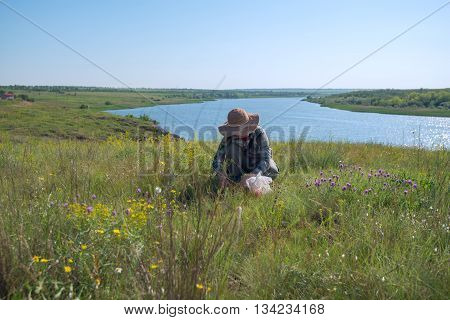 Woman in a straw hat gathers herbs in the prairies desert next to a large river. Wonderful sunny day. Azov steppes Ukraine.