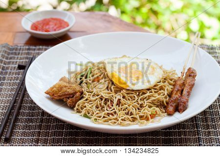 Nasi Goreng with fried egg chicken Indonesian stir fried noodles Outdoor background.