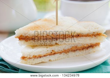Peanut butter sandwiches toasts on white plate Outdoor tropical background.