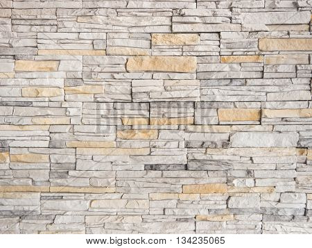 a wall from an artificial gray stone facade with rough fractured surfaces as background