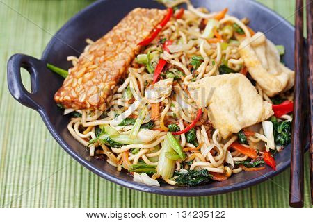 Mi gorengmee goreng Indonesian cuisine spicy stir fried noodles with tempeh and assortment of asian sauces