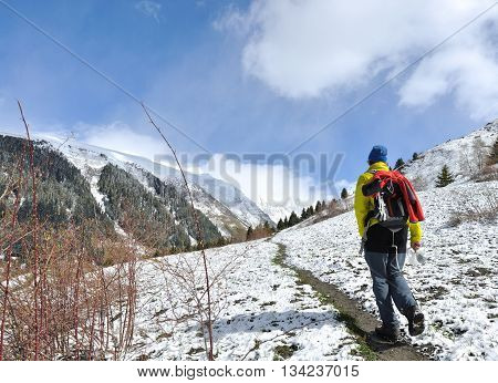 hiker with bag walking in a footpath in mountain