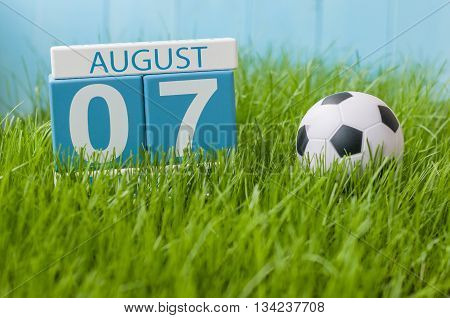 August 7th. Image of august 7 wooden color calendar on green grass lawn background with soccer ball. Summer day. Empty space for text.