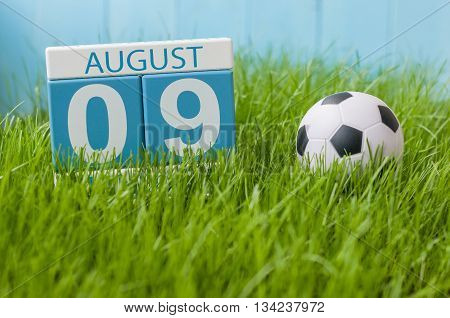 August 9th. Image of august 9 wooden color calendar on green grass lawn background with soccer ball. Summer day. Empty space for text.