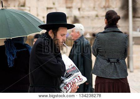 Jerusalem, Israel - March 24, 2011: Orthodox jew lights a cigarette near Western Wall in Jerusalem Old City