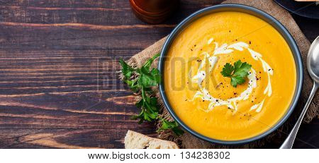Pumpkin and carrot soup with cream and parsley on dark wooden background Top view Copy space.