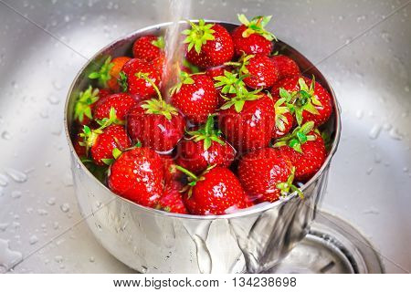 Bowl of organic strawberry in the sink under running water.