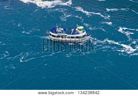 Niagara Fall, USA - April 30, 2015: Ferry on the Niagara River. A view from American side. Niagara River is a river from Lake Ontario to Lake Erie. It is a natural border between Canada and the USA. Tourists on board