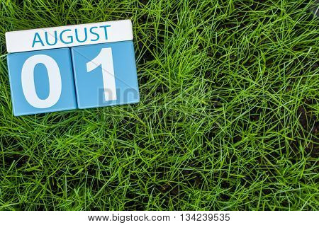 August 1st. Image of august 1 wooden color calendar on green grass lawn background. Summer day. Empty space for text.