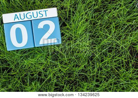 August 2nd. Image of august 2 wooden color calendar on green grass lawn background. Summer day. Empty space for text.